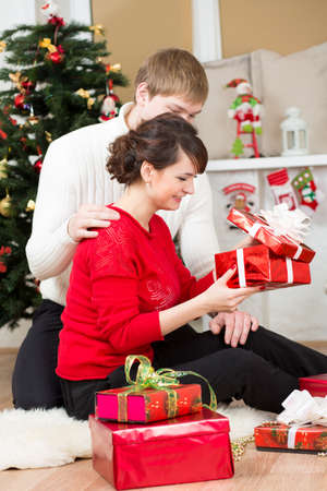 Young couple with gift in front of Christmas tree  at home Stock Photo - 20962142