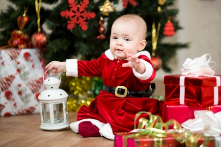 traditional gifts: baby girl dressed as Santa Claus in front of Christmas tree with gifts Stock Photo