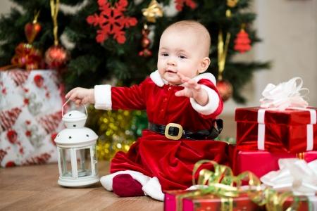 baby kerst: baby meisje verkleed als Santa Claus in de voorkant van de kerstboom met geschenken