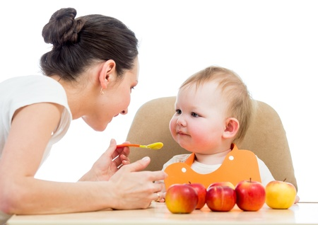 young mother spoon feeding her baby girl photo