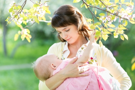 beautiful breasts: young mother breast feeding her baby girl in garden