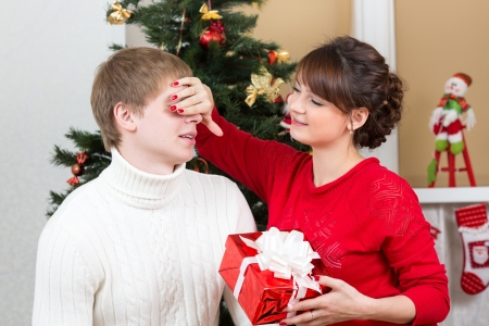 happy woman closing man eyes by her hands with gift Stock Photo - 21075157