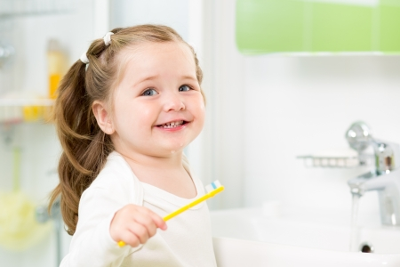 cepillarse los dientes: Sonriente ni�a ni�o cepillarse los dientes en el ba�o Foto de archivo