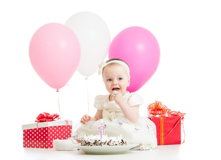 Smiling baby girl eating cake on first birthday photo