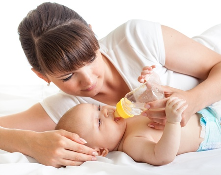 young mother feeding her baby from bottle photo