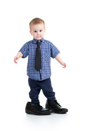 to try: kid boy trying on father shoes Stock Photo
