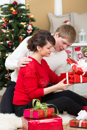 Young couple with gifts in front of Christmas tree  at home photo