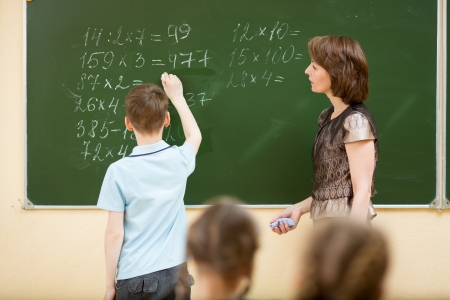 children writing: School kids in classroom at math lesson