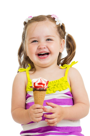 happy kid girl eating ice cream in studio isolated photo