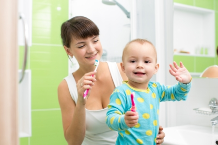 mother with baby brushing teeth photo