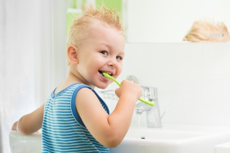 child boy brushing teeth in bathroom photo