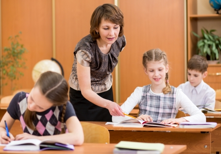 learning process: School kids work at lesson  Teacher controlling learning process  Stock Photo