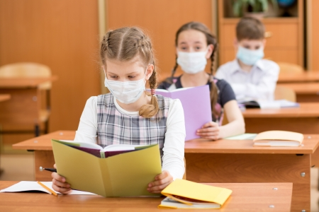 school kids with protection mask against flu virus at lesson photo