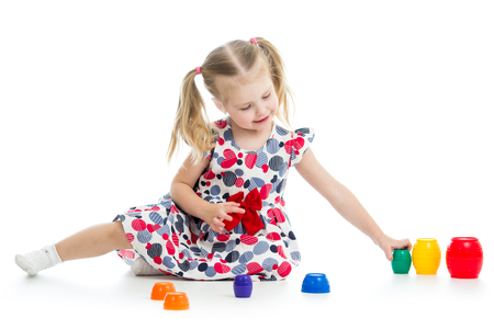 girl child playing with cup toys, isolated over white photo