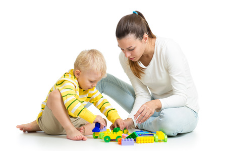 kid boy and mother play together with construction set toy photo