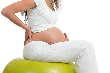 pregnant woman sitting on fit ball with hand on her back, isolated photo