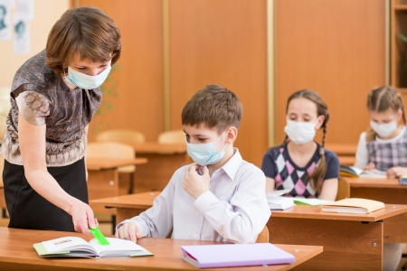 quarantine: school kids and teacher with protection mask against flu virus at lesson