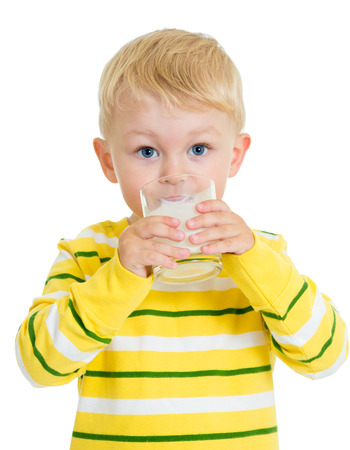 Kid boy drinking milk or yoghurt from glass photo