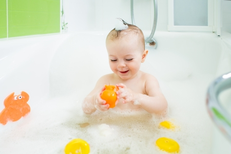 baby bath: smiling baby girl taking bath and playing with toys