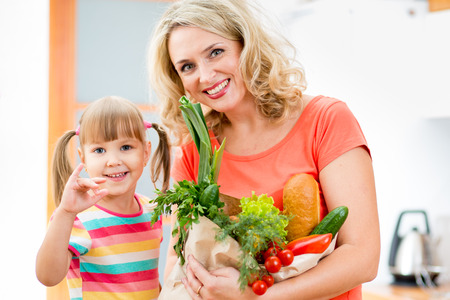 mother and kid holding a shopping bag full of vegetables  on kitchen photo