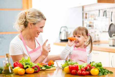 mother and her child preparing healthy food and having fun photo