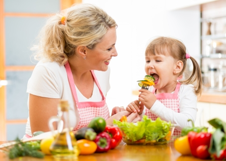 Madre que introduce al ni�o hija verduras en la cocina photo