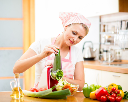 kitchen device: woman cutting vegetables with device at the kitchen table