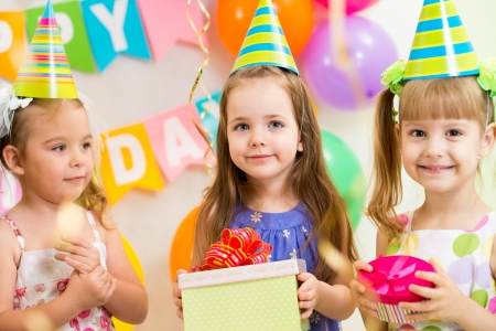 pretty children with gifts on birthday party photo