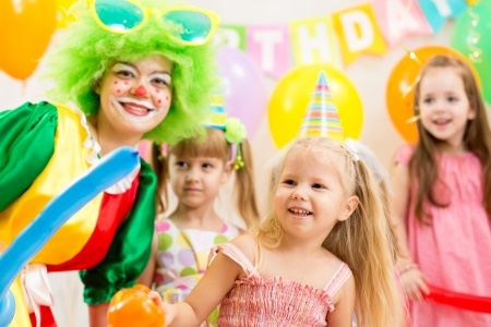 kids birthday party: kids group and clown on birthday party