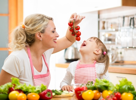 mother preparing dinner and feeding kid  tomato in kitchen photo