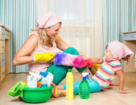mother with kid cleaning room and having fun photo