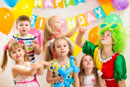 kids birthday party: jolly kids group with clown celebrating  birthday party Stock Photo