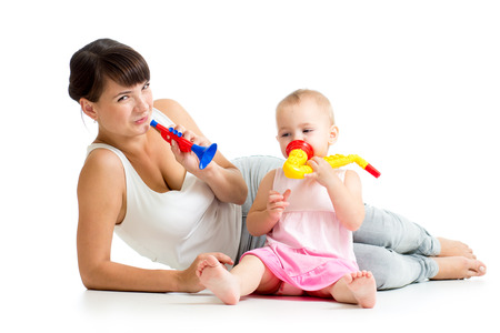 Mother and baby girl having fun with musical toys  Isolated on white background photo