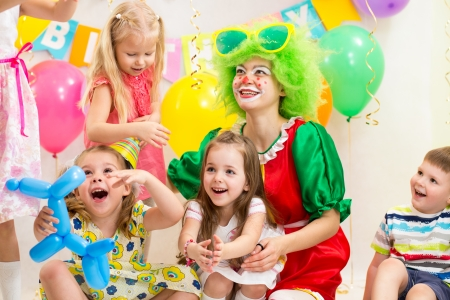 jolly children with clown on birthday party photo