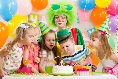 balloons party: kids with clown celebrating birthday party and blowing candle on cake Stock Photo