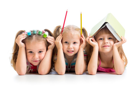 kids with book, pencils and paints on their heads photo