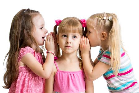 niños platicando: niños amigas que comparten un secreto aislados Foto de archivo