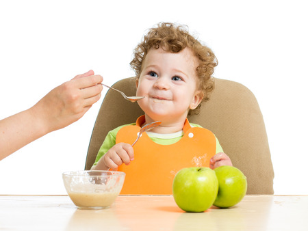 mother hand spoon feeding baby boy Stock Photo - 23177196