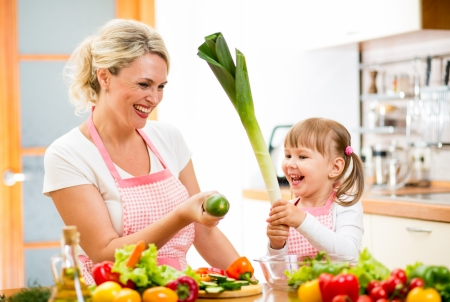 mother and kid preparing healthy food and having fun photo