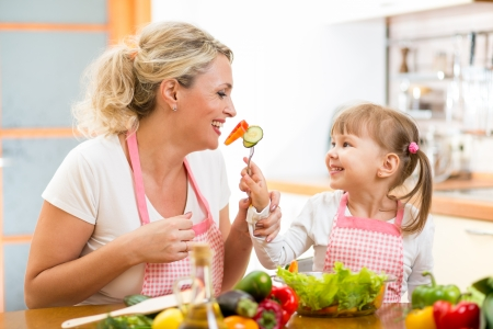 kid daughter feeding mother vegetables in kitchen photo