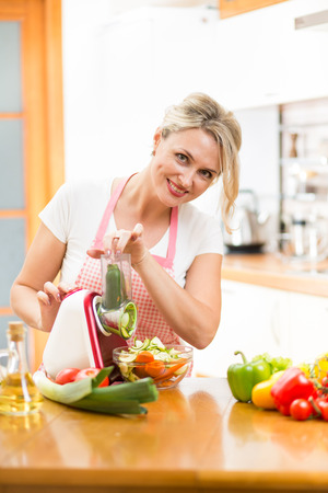 kitchen device: Cute woman cutting vegetables with device at the kitchen table Stock Photo
