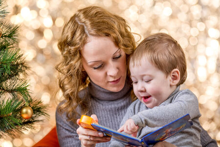 christmas baby: mother reading book to kid at Christmas tree