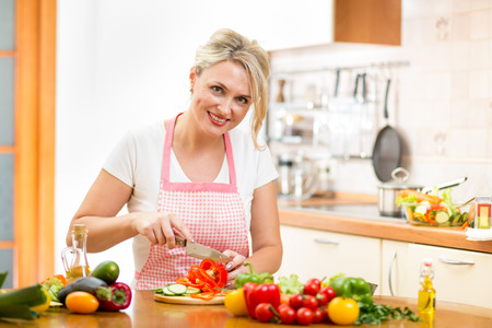 slicing: Cute woman cuts paprika for salad sitting at the kitchen table
