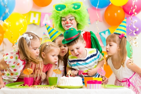 kids with clown celebrating birthday party and blowing candle on cake Stock Photo - 23338686