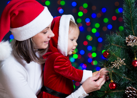 baby girl with mother decorating Christmas tree on bright background Stock Photo - 23378958