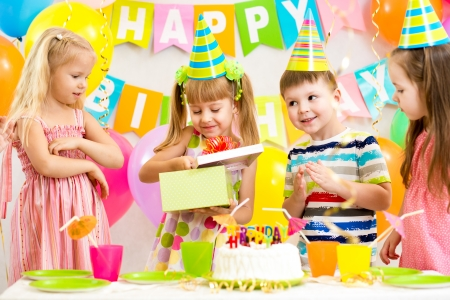 baby open present: happy kids celebrating birthday party