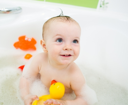 baby girl taking bath and playing with toys photo