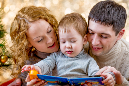 Family at christmas tree. Parents read book to kid. photo