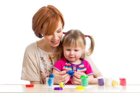 kid girl and mother playing colorful clay toy photo