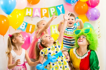 party balloons: jolly kids group with clown celebrating  birthday party Stock Photo